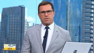 Rodrigo Bocardi de terno cinza, gravata azul escura com um computador com logo da Globo