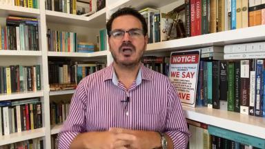 Rodrigo Constantino de camisa com livros ao fundo