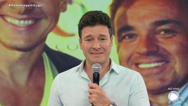 Rodrigo Faro chorando no palco do Hora do Faro com imagem dele com Gugu no telão