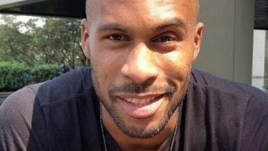 O modelo Rodrigo Moraes sorrindo para a foto