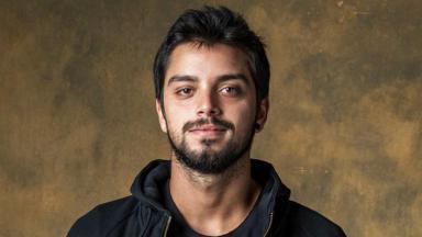 O ator Rodrigo Simas com leve sorriso