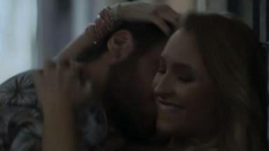 Rubinho beijando o pescoço de Carine que sorri