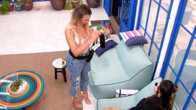 Sarah em pé gesticulando e conversando com Juliette sentada em poltrona na área externa da casa do BBB21