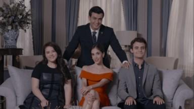 Daniel em pé e Paola sentada ao lado dos filhos para tirarem uma foto, cena da série A Usurpadora