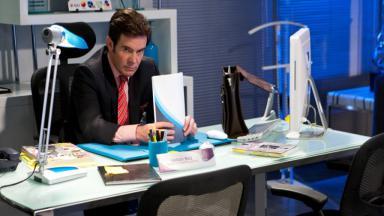 Nelson sentado à mesa do escritório, pensativo