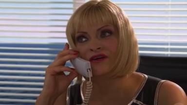 Cena de Coração Indomável com Carol sentada conversando no telefone