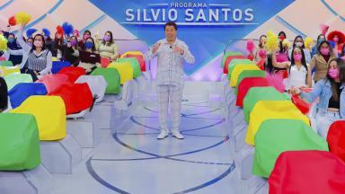Silvio Santos na volta de seu programa rindo com braços abertos