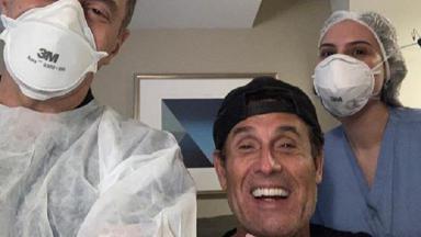 Sérgio Mallandro sorrindo ao lado dos profissionais do hospital