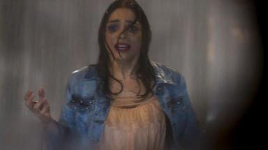 Shirlei toda molhada, com as mãos levantadas e olhar de terror