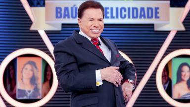 O apresentador Silvio Santos, com terno e gravata, sorri no palco do seu programa no SBT