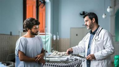 Os atores Kelner Macêdo e  Brun Garcia se olham em cena de Sob Pressão no hospital