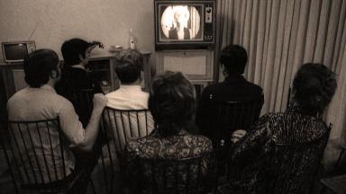 Pessoas assistindo à televisão antiga