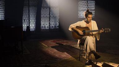 Tiago Iorc sentado com o violão na mão