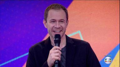 Tiago Leifert com microfone na mão e sorrindo