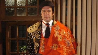 Cena de Ti Ti Ti, com Ariclenes em pé vestido de Victor Valentim, com roupa de toureiro