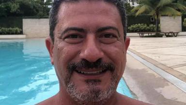 Tom Veiga sorrindo na piscina