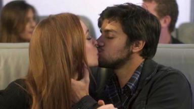 Jonatas beija Eliza dentro do avião em cena final da novela Totalmente Demaislo enquanto olha para o amado