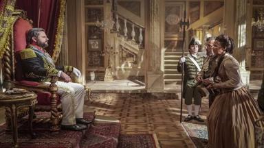 Dom Pedro II sentado no trono enquanto atende Quinzinho e Clemência