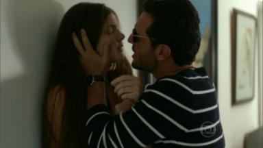 Alex pressionando Angel contra parede, com as mãos no rosto dela