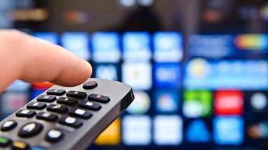 Foto de um controle remoto e televisores ao fundo
