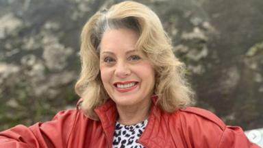 Vera Fischer sorrindo de jaqueta vermelha