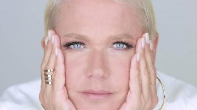 Xuxa está com as mãos no rosto