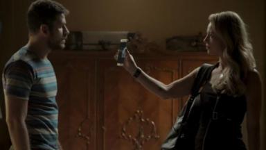 Jeiza ergue o celular na direção de Zeca que olha atentamente para a tela