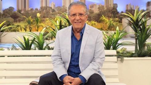 Carlos Alberto de Nóbrega sorridente, sentado no banco de A Praça é Nossa