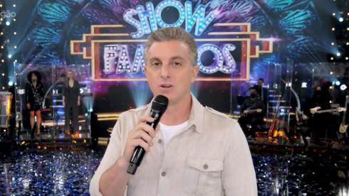 Luciano Huck segurando microfone no palco do Domingão da Globo