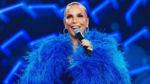 Ivete Sangalo de roupa com fios azuis e microfone na mão sorrindo