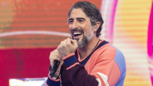 Marcos Mion sorrindo e segurando microfone
