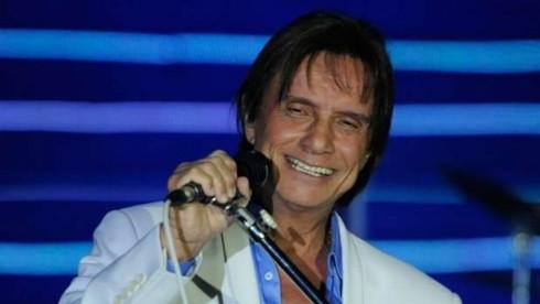 Roberto Carlos, de camisa azul e terno branco, segura microfone e sorri em show