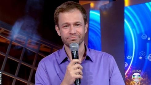 Tiago Leifert de camisa lilás e microfone na mão