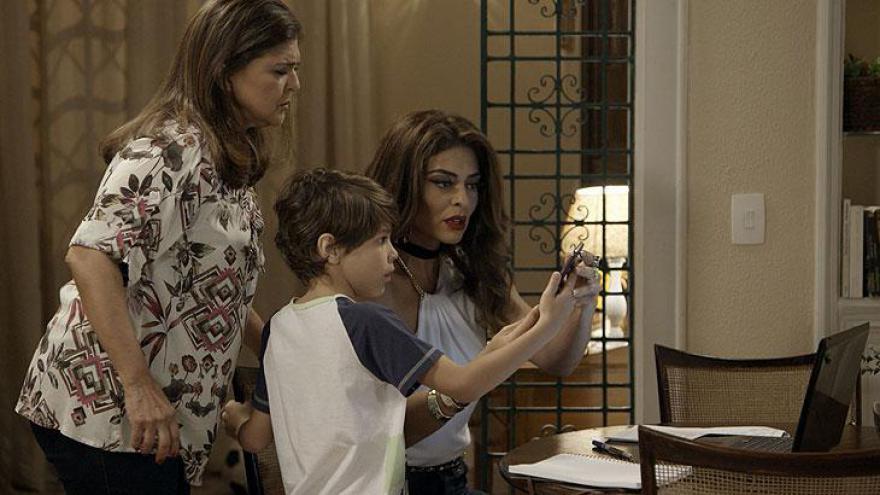 Aurora e Bibi olham a foto da bandida ao lado de Caio