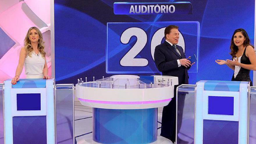 """Silvio Santos recebe a jornalista Érica Reis (apresentadora do """"Leitura Dinâmica"""", da RedeTV!) e a atriz Carol Santos (apresenta o """"Master Game"""") em um inédito """"Jogo das 3 Pistas""""."""