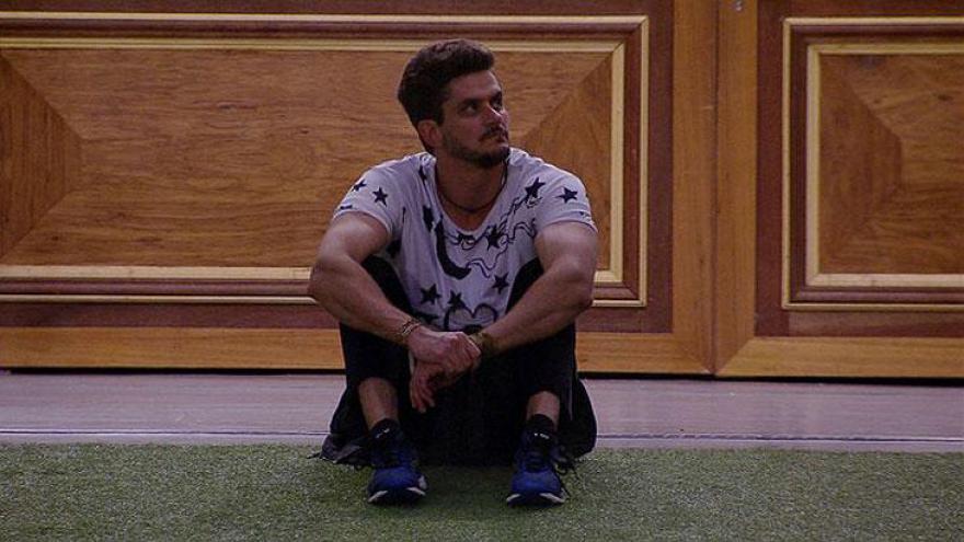 Marcos observa competição sentado na grama na área externa da casa do