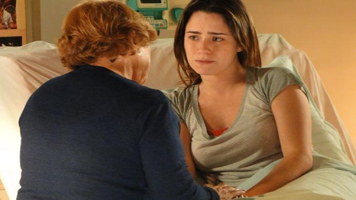 Iná segura a mão de Ana enquanto conversam no quarto do hospital