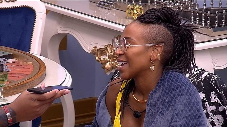 Karol Conká sentada com Nego Di colocando um celular perto da boca dela