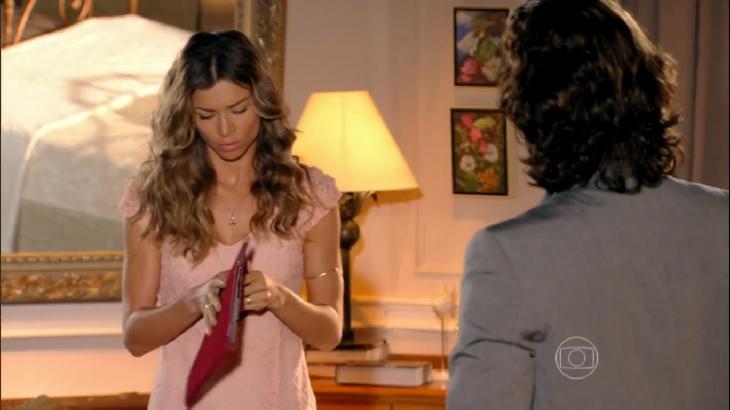 Cena de Flor do Caribe com Ester abrindo um dossiê contra Cassiano com Alberto olhando