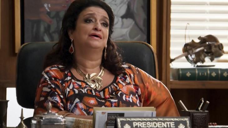 Cena de Haja Coração com Teodora sentada em sua cadeira de presidente