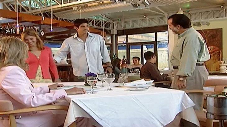 Cena de Laços de Família com Helena sentada à mesa, Miguel, Edu e Camila de pé, no restaurante