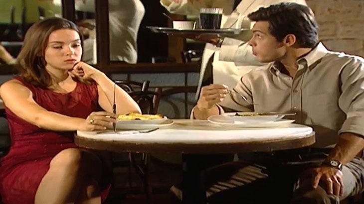 Cena de Laços de Família com Clara e Fred sentados num restaurante com cara de bravos