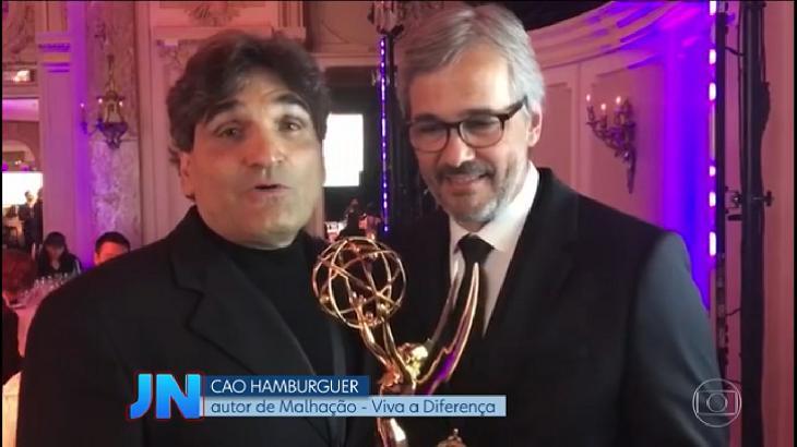 """Cao Hamburger e Paulo Silvestrini com o prêmio do Emmy Internacional Kids, sendo entrevistados pelo """"Jornal Nacional"""""""