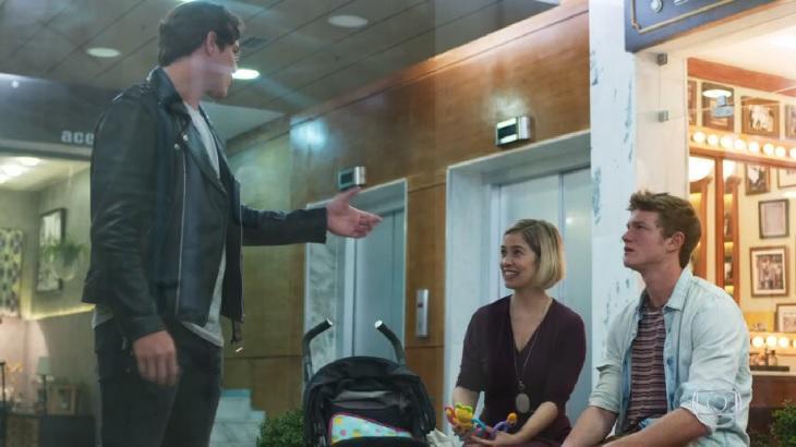Rui de pé, conversando com Lígia e Filipe, sentados.