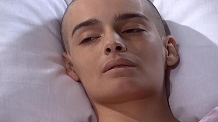 Marcela deitada na cama do hospital, abatida