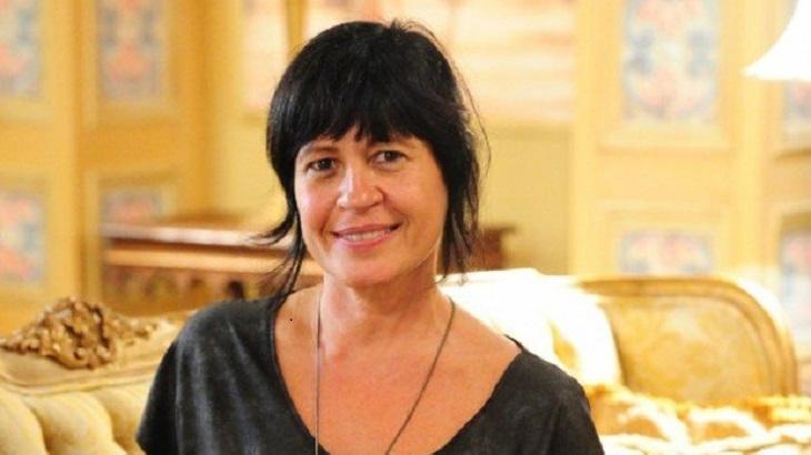 Thelma Guedes sentada num sofá posa para foto sorrindo
