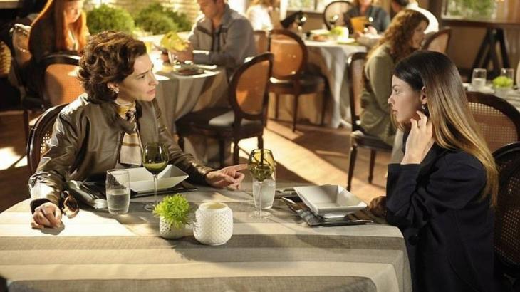 Vitória e Alice sentadas de frente uma para outra em restaurante