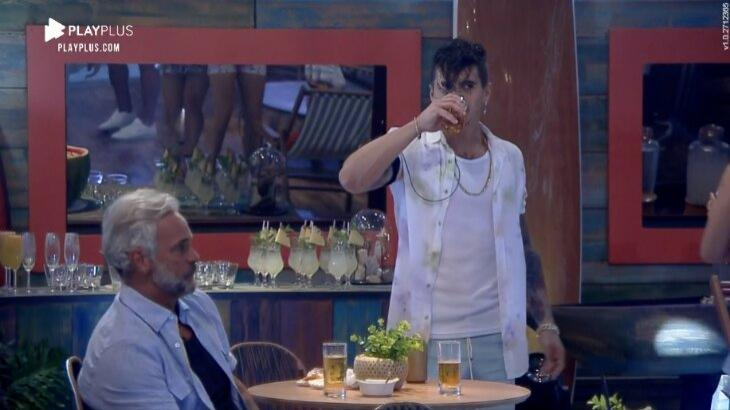 Mateus sentado na mesa, enquanto Biel se aproxima bebendo cerveja