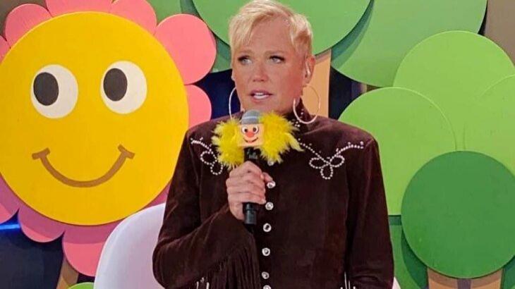 Xuxa, com microfone na mão, comanda brincadeiras