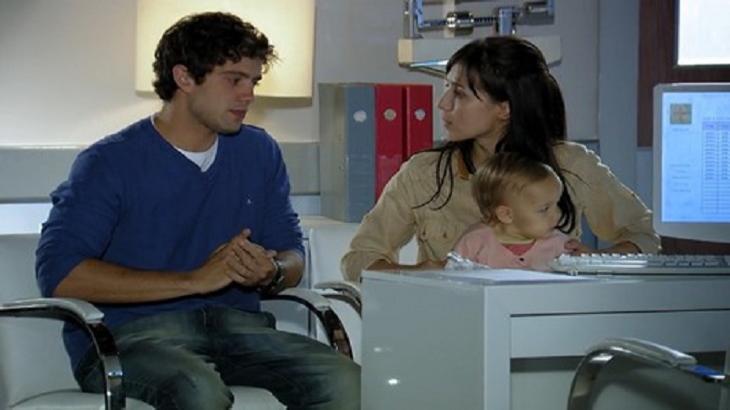 Cena de A Vida da Gente com Rodrigo e Manu sentados, olhando um para o outro e ela com Julia no colo